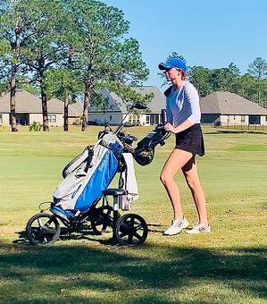 Hope Waggoner, Player Development Member, pushes clubs on the course – Greystone