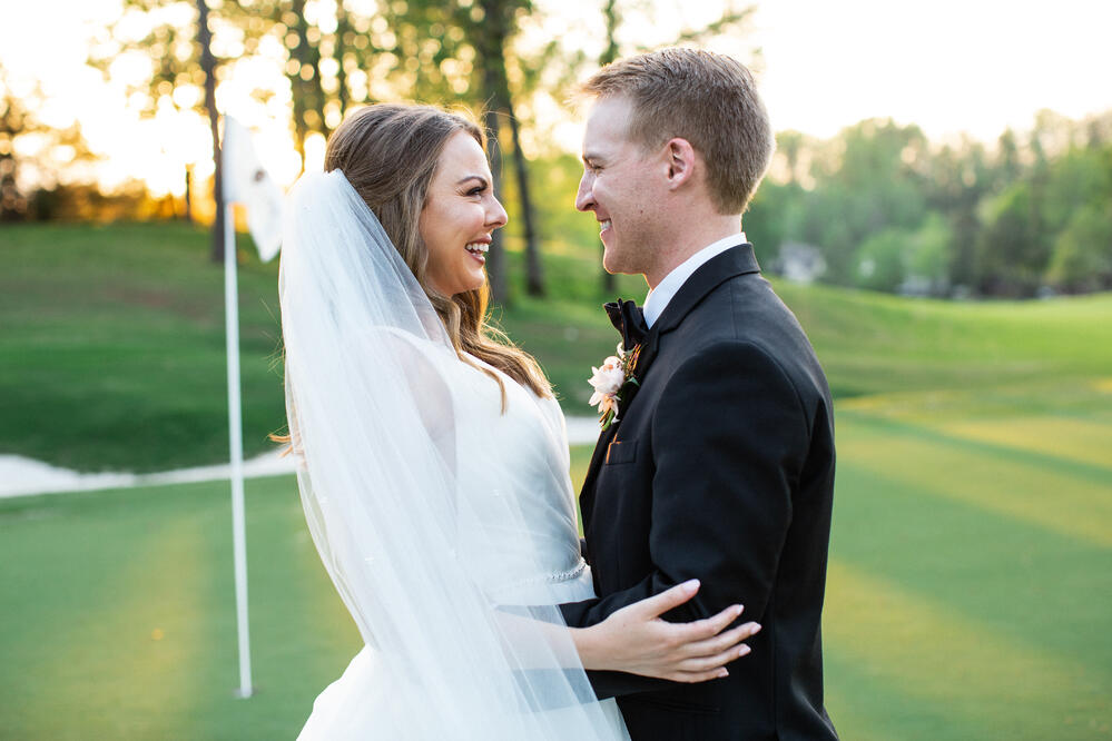 the satterfields on the green at greystone, embracing on their wedding day